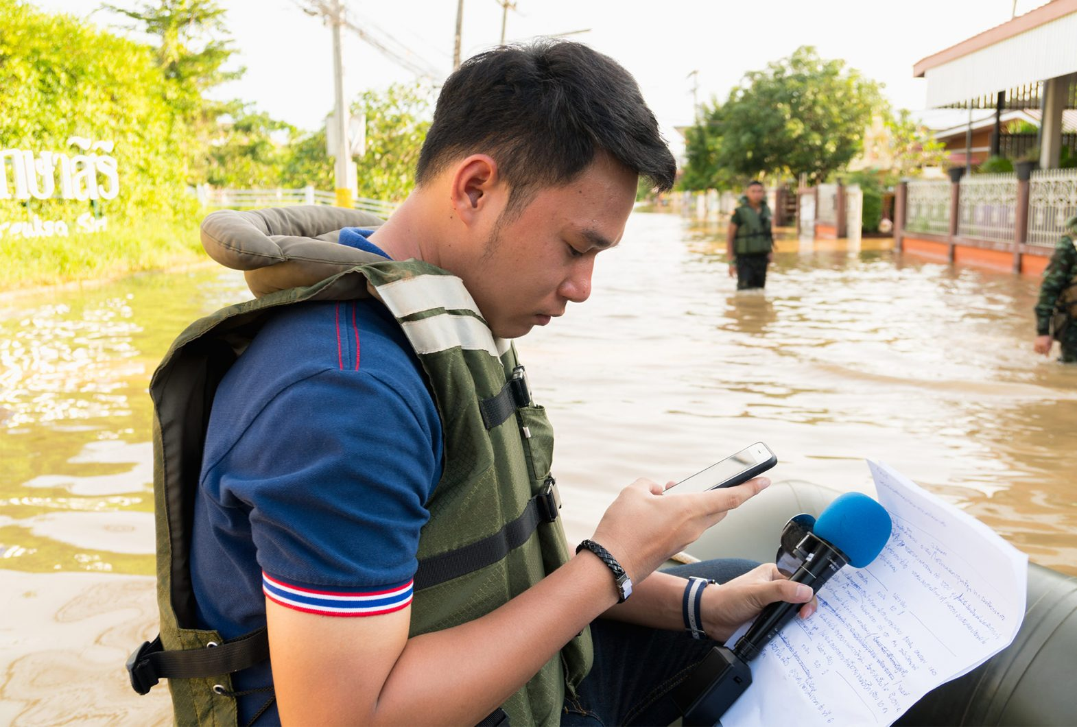 Person looking at phone while wading in a flood.